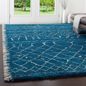 Belgian 8' x 10' area rug with diamond pattern in bright blue and white with fringe in living room
