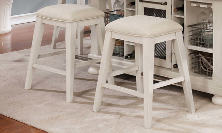 Closeout counter height stools in brushed white finish with neutral upholstery cushions