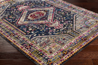 Colorful and unique 5 x 7 Turkish rug with hints of white and blue from the Surya Alchemy Collection on wood floor