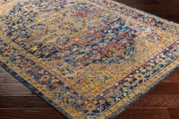 Unique Turkish rug with distinct yellow, blue and red pattern from the Surya Alchemy Collection on wood floor