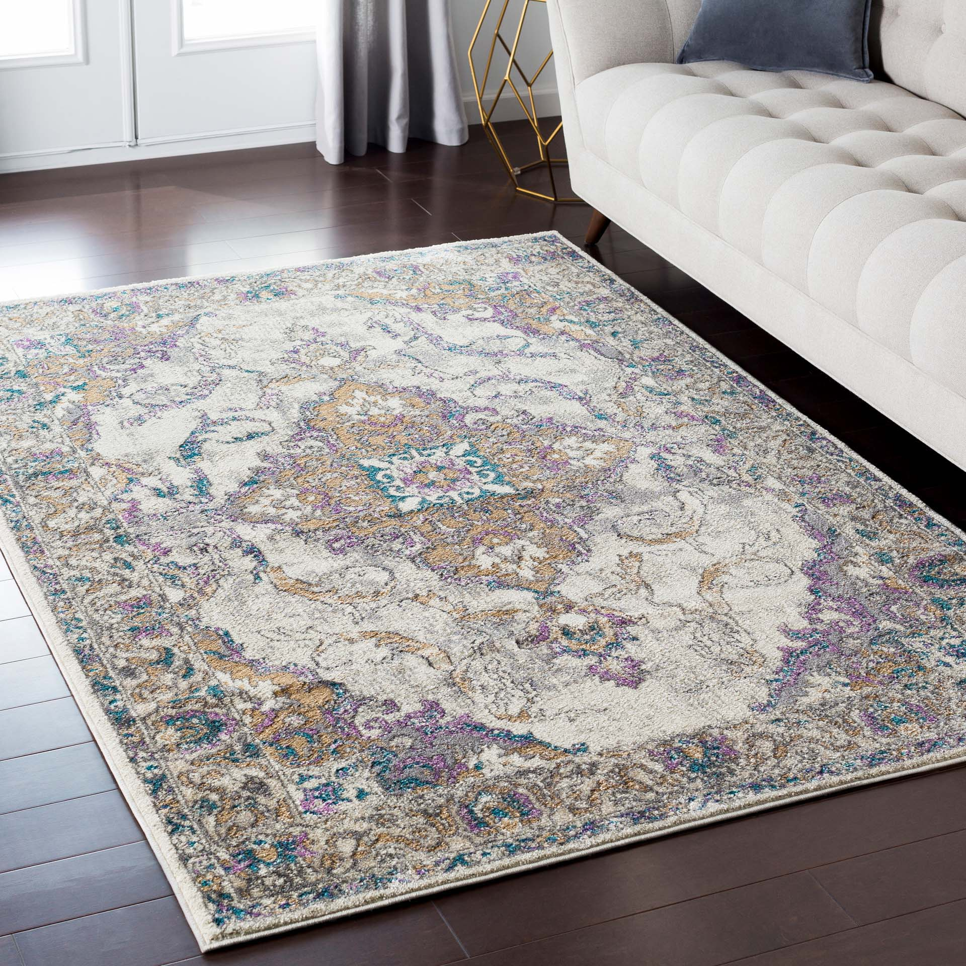 Classic ivory Turkish area rug with gray, purple and aqua ribbon and floral pattern in living room