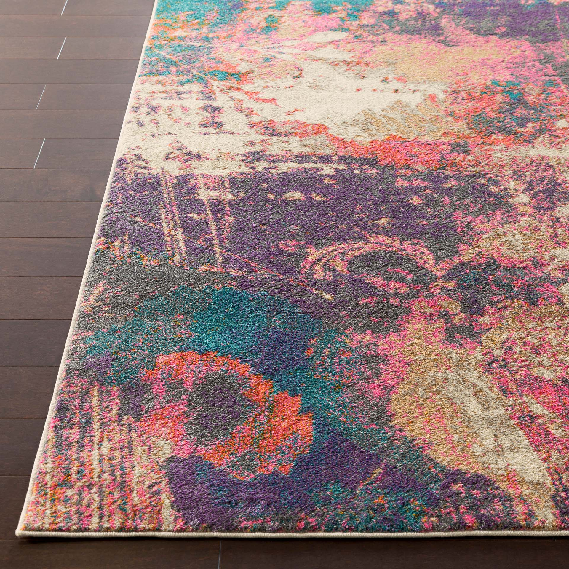 Abstract art inspired Turkish area rug with splashes of cream, purple, pink, orange and teal on wood floor