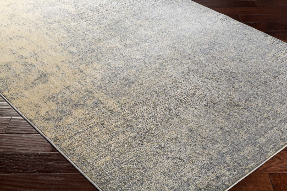 Neutral toned machine made Egyptian area rug with splashes of beige, cream and gray on wood floor