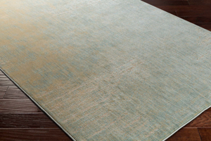 Modern machine made Egyptian area rug with splashes of beige, cream and green on wood floor