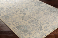 Neutral machine made Egyptian area rug in beige with hints of gray and green on wood floor
