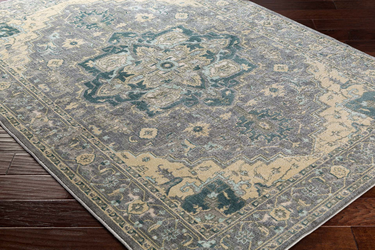 Neutral tone machine made area rug from Egypt with hints of gray, green and beige on wood floor