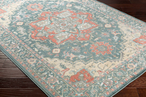 Neutral tone machine made area rug from Egypt with hints of green, beige and gray on wood floor