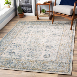 Classic machine woven area rug in beige with blue and green accentsin living room