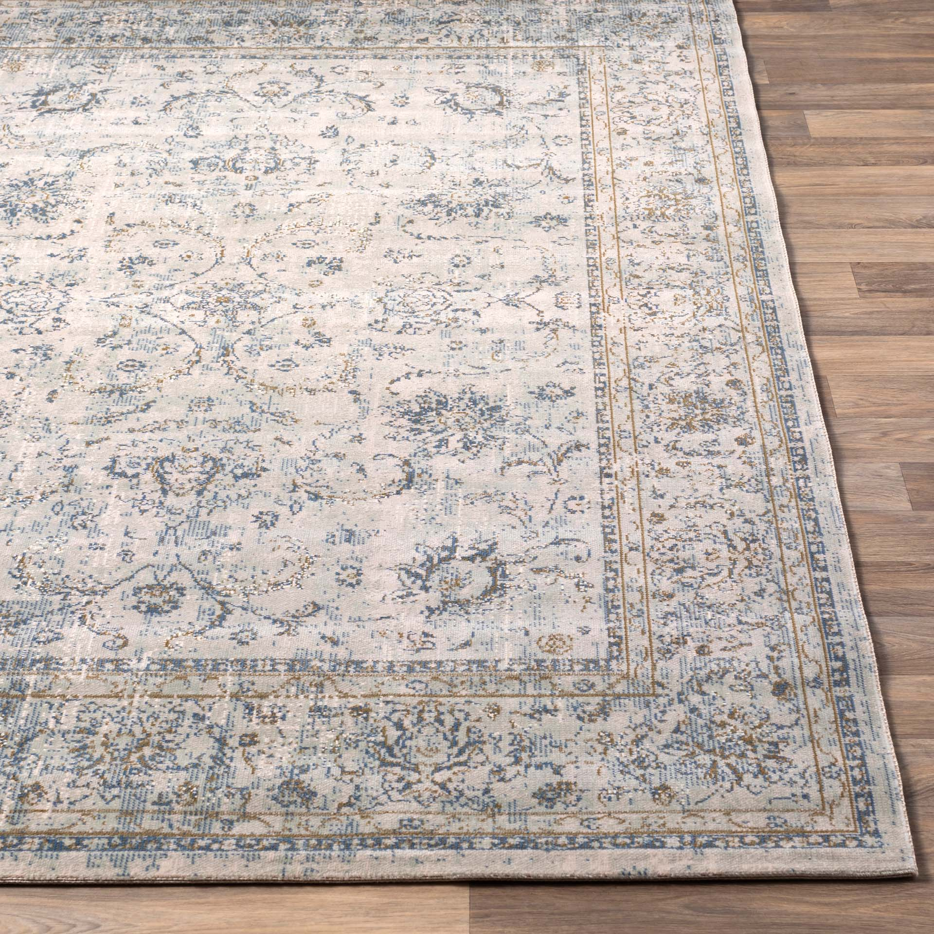 Classic machine woven area rug in beige with blue and green accents	on light wood floor
