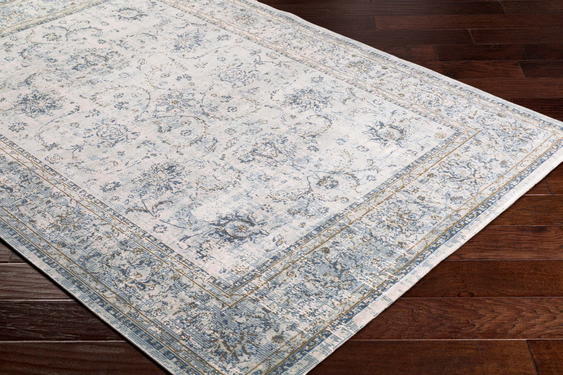 Classic machine woven area rug in beige with blue and green accents on cherry wood floor