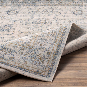 Classic machine woven area rug in beige with blue and green accents on light wood floor - Backing Shot