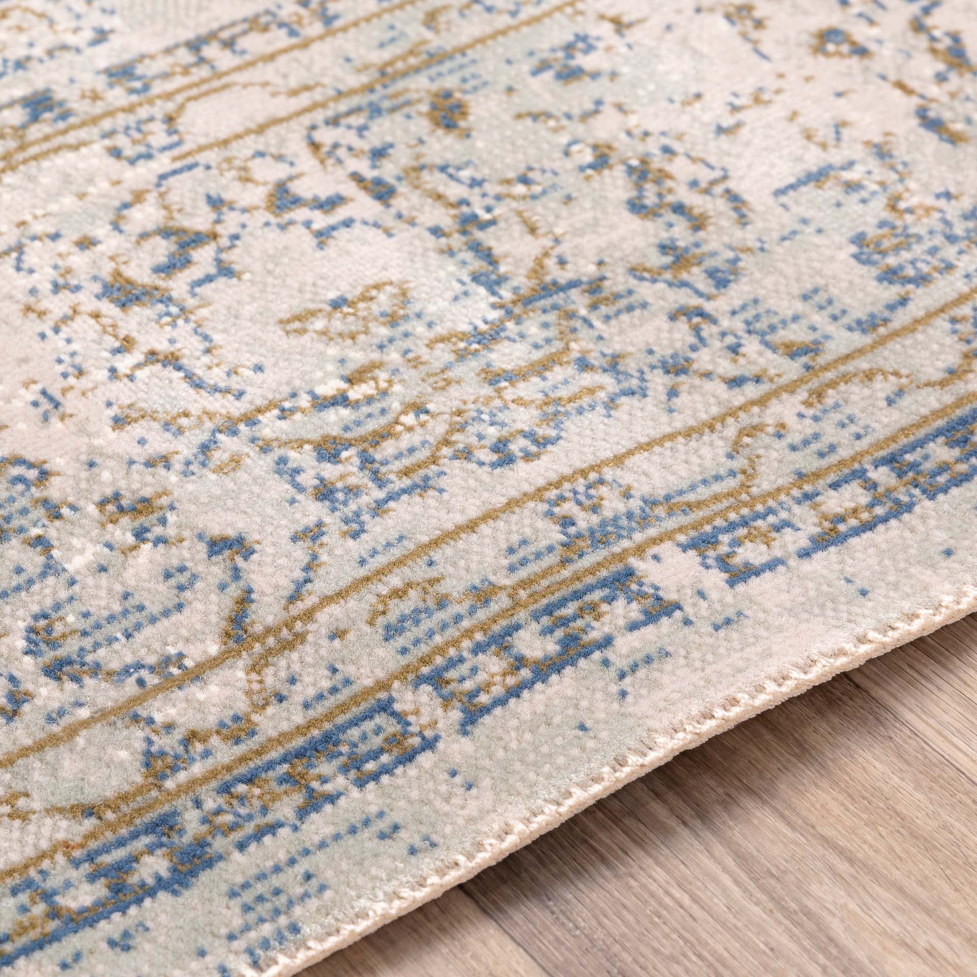 Classic machine woven area rug in beige with blue and green accents on light wood floor - Detail Shot