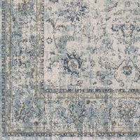Classic machine woven area rug in beige with blue and green accents on light wood floor - Close up