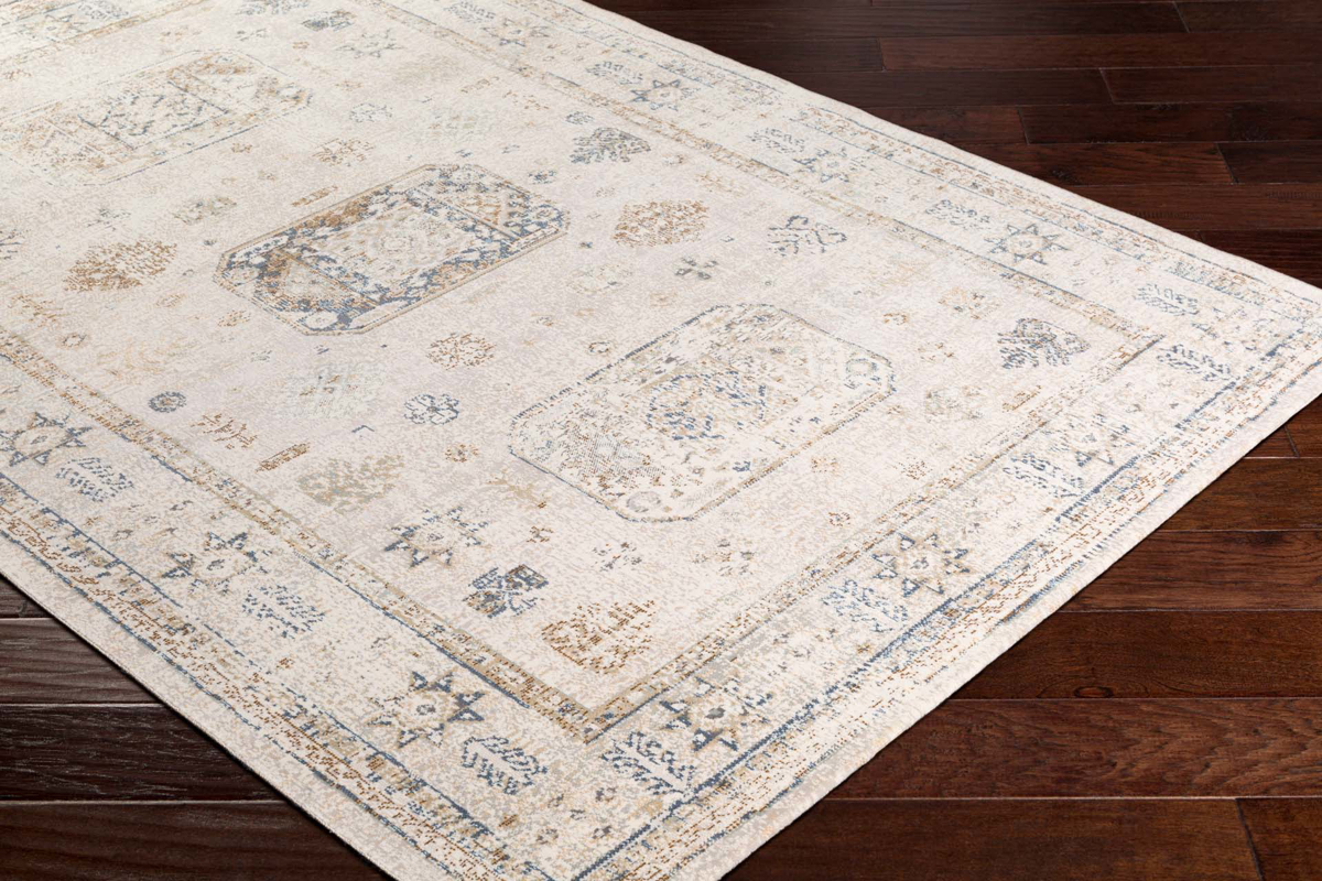 Neutral toned machine made area rug from Israel in beige with taupe, dark brown and green accents on wood floor