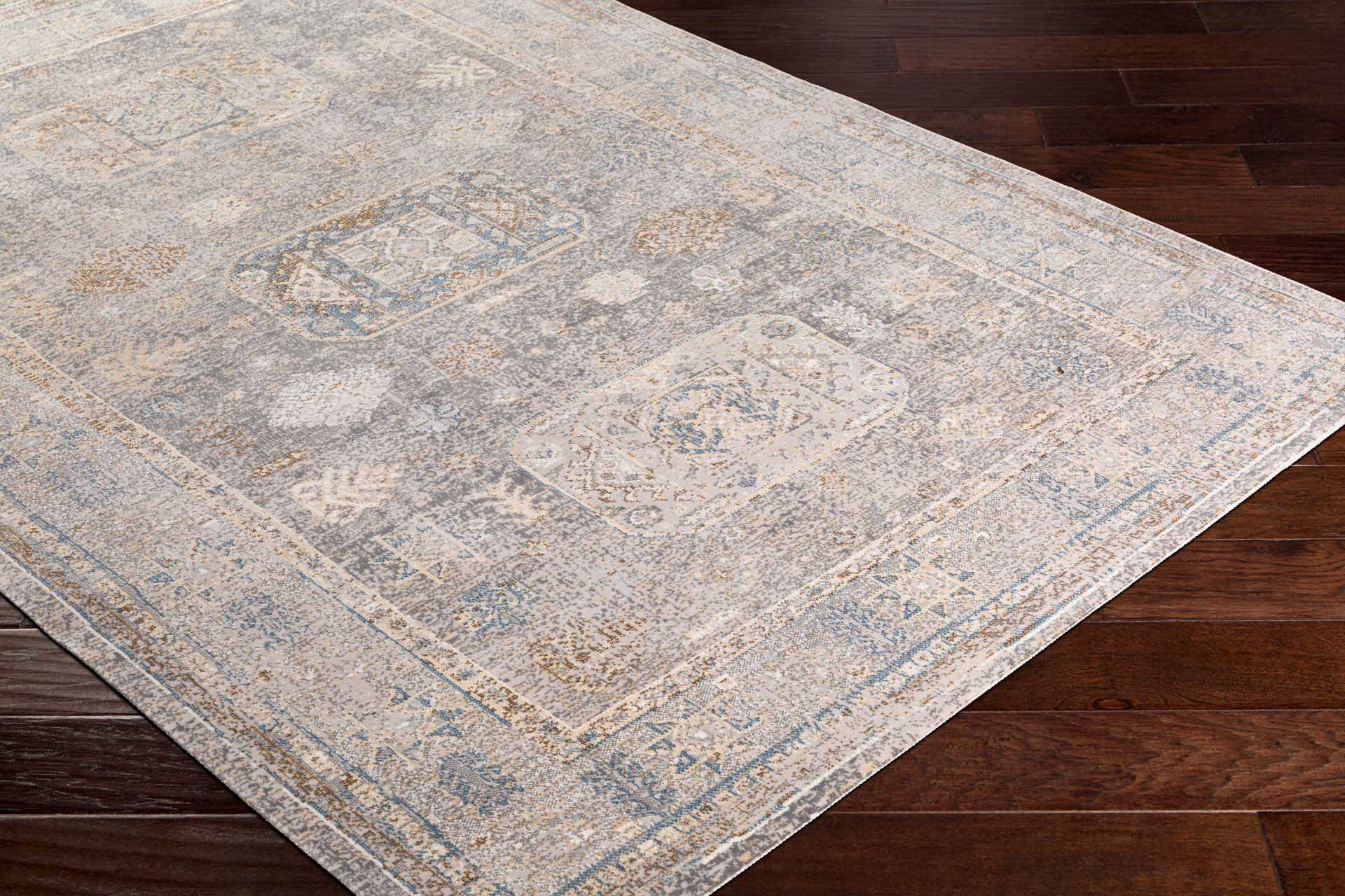Neutral machine-made area rug from Israel with hints of beige, gray, blue and brown	on wood floor