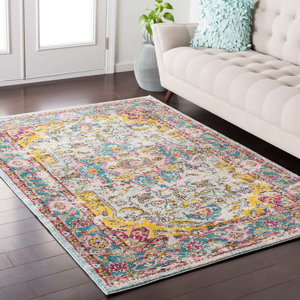 Trendy colorful 5x7 Turkish rug with hints of yellow, pink and blue from the Surya Anika Collection on wood floor in living room