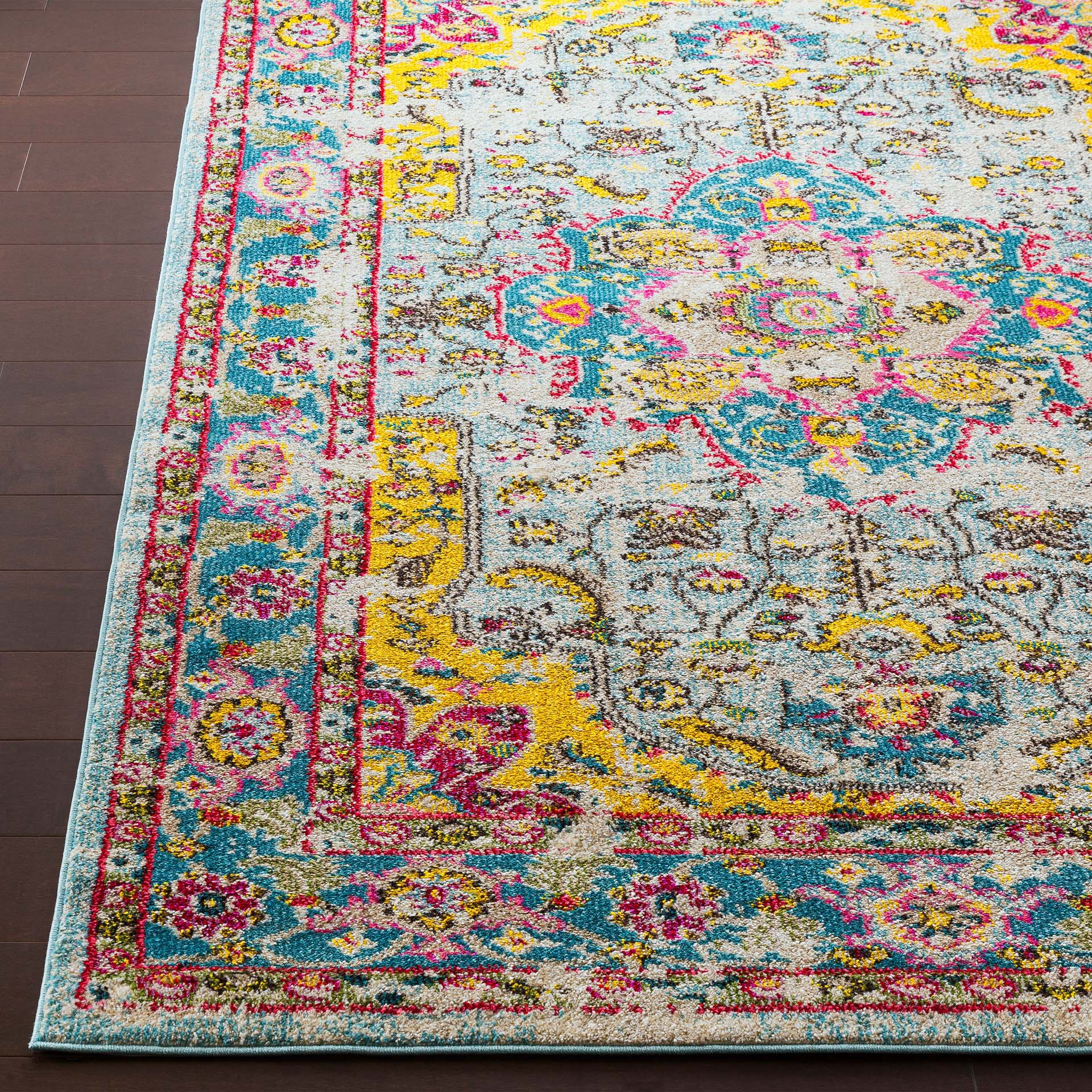 Trendy colorful 5x7 Turkish rug with hints of yellow, pink and blue from the Surya Anika Collection on wood floor - Close up Shot