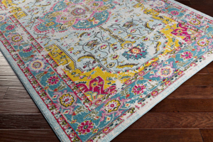 Trendy colorful 5x7 Turkish rug with hints of yellow, pink and blue from the Surya Anika Collection on wood floor - Side Shot