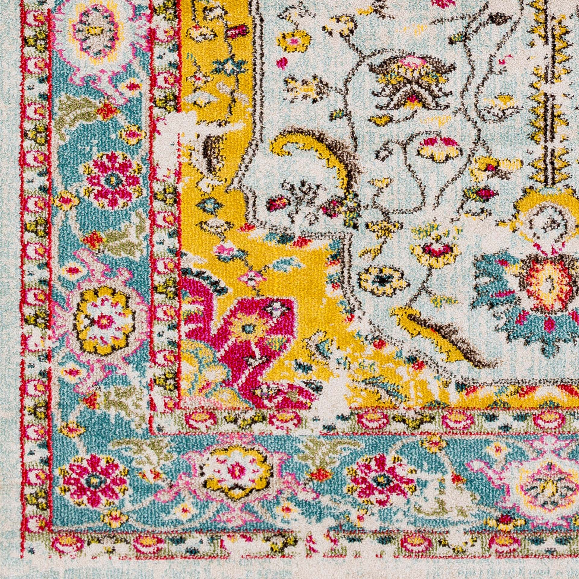Trendy colorful 5x7 Turkish rug with hints of yellow, pink and blue from the Surya Anika Collection on wood floor - Detailed Shot