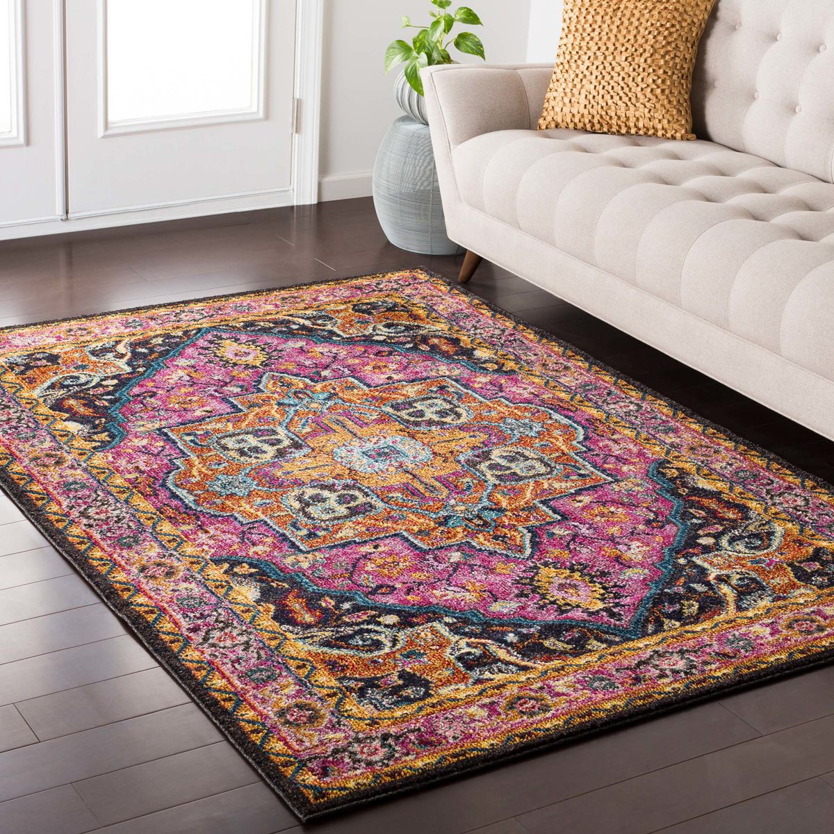 Trendy colorful 5x7 Turkish rug with hints of pink from the Surya Anika Collection on wood floor in living room