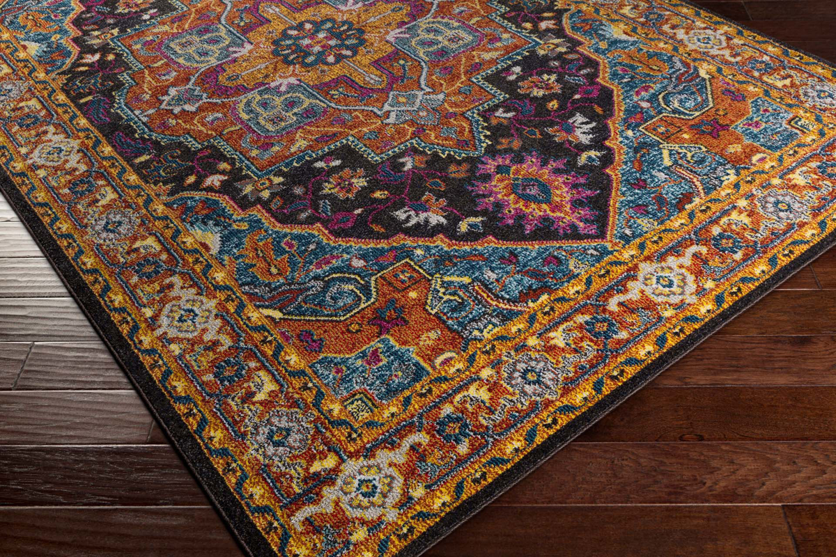 Trendy colorful Turkish rug with hints of blue and yellow from the Surya Anika Collection - Side Shot on Wood Floor