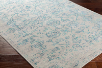 Machine made area rug from Israel in gray with teal flower accents on wood floor