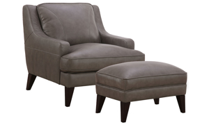 Comfortable armchair with ottoman in gray top-grain leather atop dark wood feet.