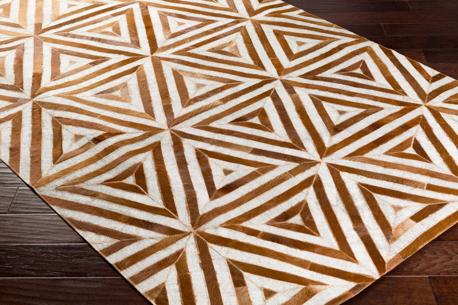 Handcrafted Surya Medora rug featuring hair on hide from India, triangle tribal print pattern.