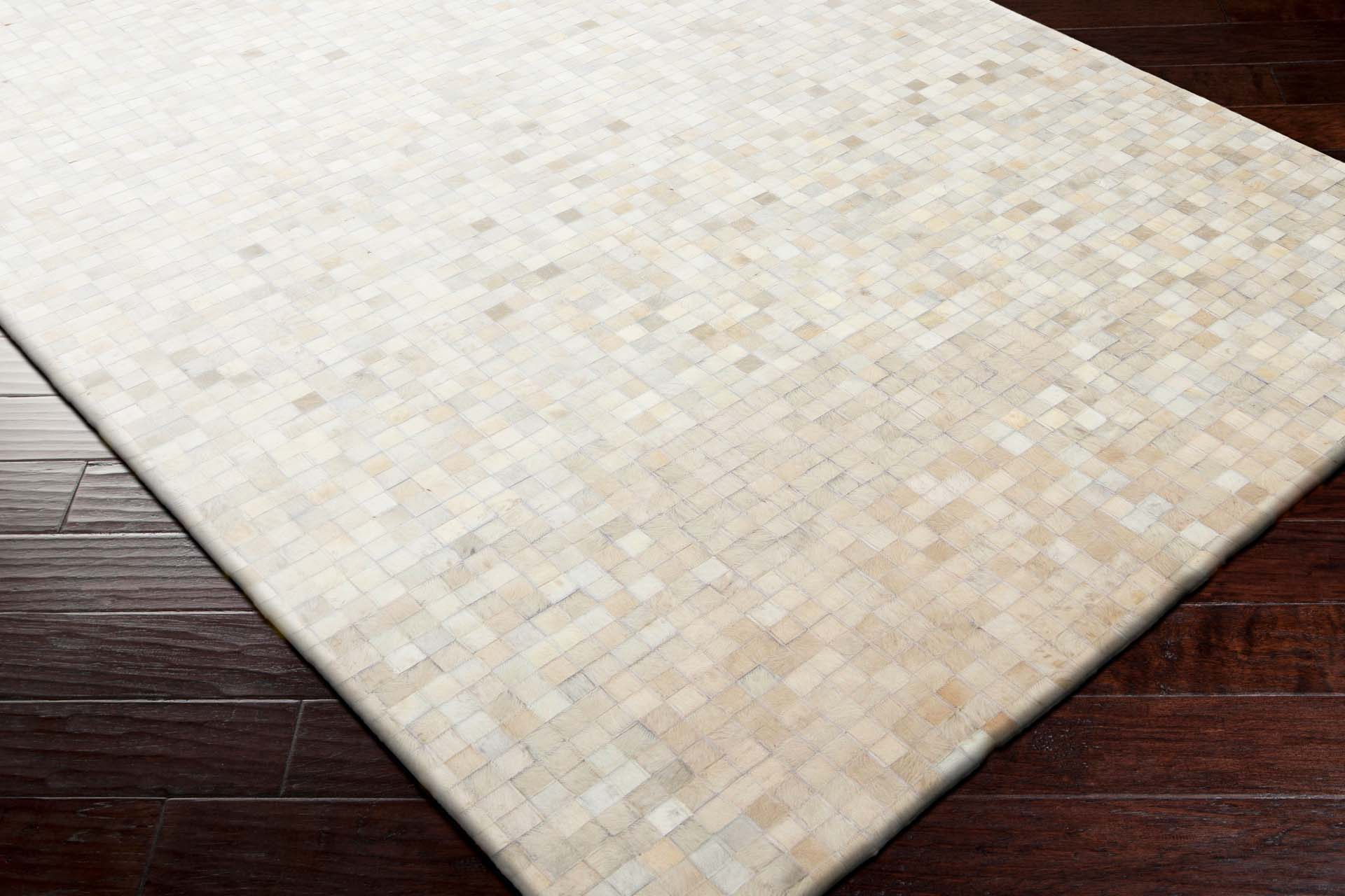Handcrafted Surya Trail rug featuring Hair on Hide from India with khaki, ivory and beige tile pattern overtones.