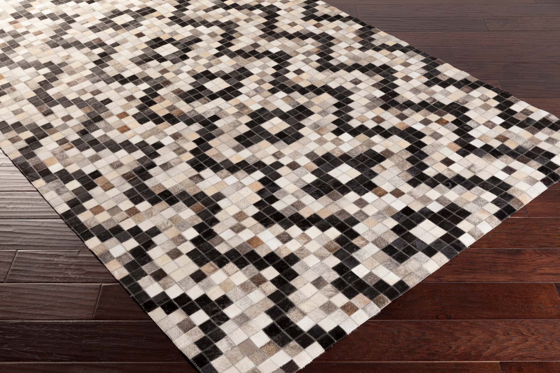 Handmade hair on hide rug from India with intricate black and gray pattern on wood floor