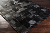 Handmade hair on hide area rug from India with black and metallic silver patchwork pattern on wood floor