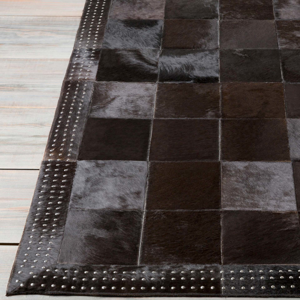 Handmade hair on hide area rug from India with black and metallic silver patchwork pattern	 - Close up