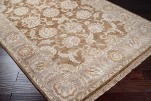 Hand knotted 5x8 rug with hints of tan and brown from the Surya Timeless Collection on wood floor