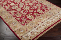 Hand knotted rug with hints of burgundy and khaki from the Surya Timeless Collection on Wood Floor