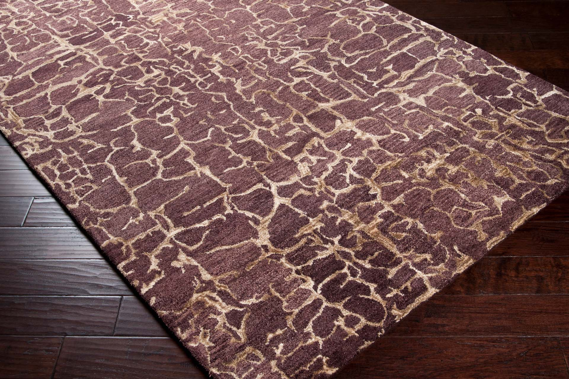 Trendy hand-tufted area rug from India with brown and tan textured pattern on wood floor