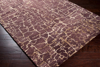 Trendy brown and tan 5x8 area rug from the Surya Banshee collection on wood floor
