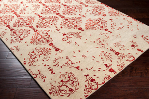 Hand-tufted beige 8' x 11' rug from India with red twist pattern on wood floor