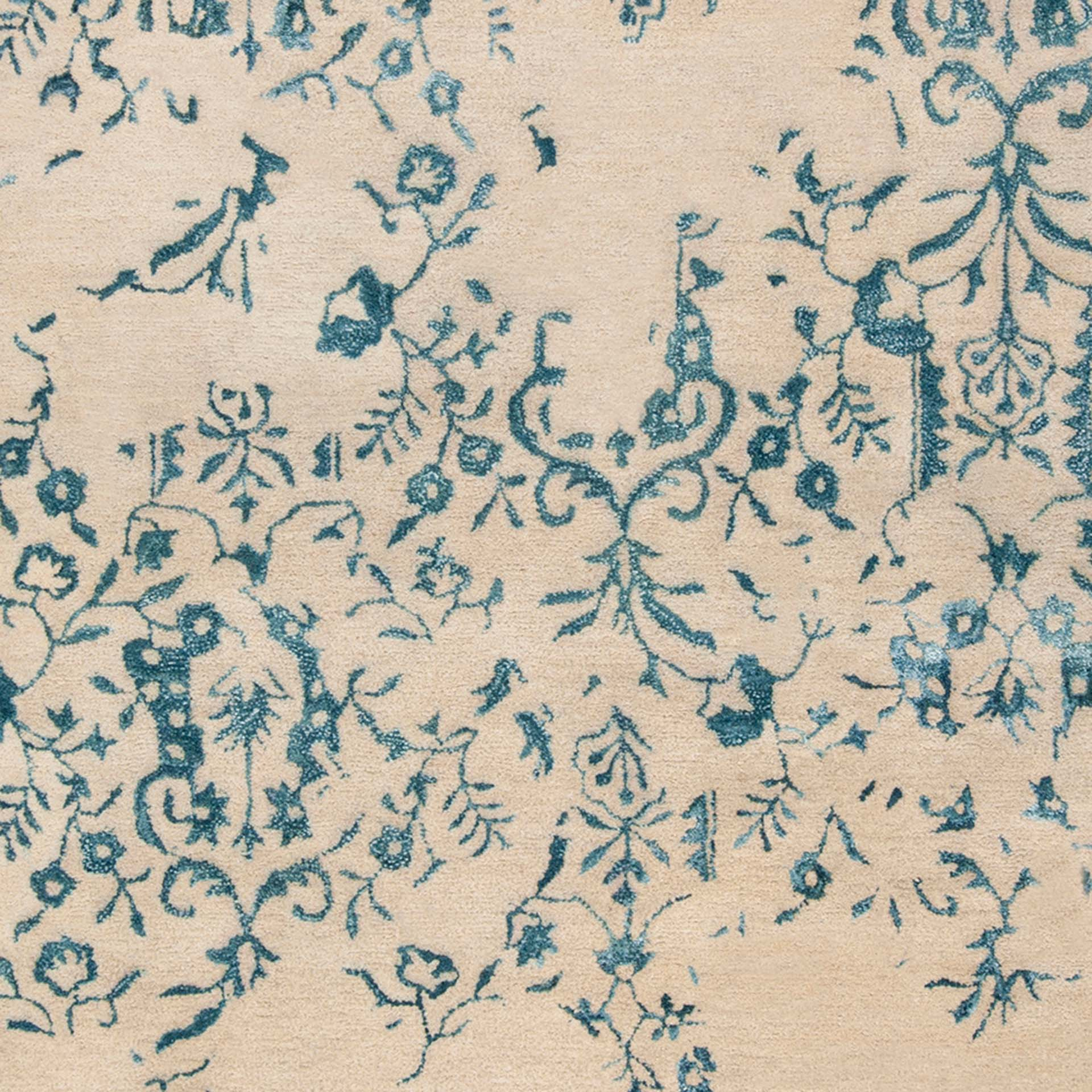 Trendy hand-tufted area rug from India with hints of blue and white from the Surya Banshee collection - Closeup of floral pattern