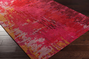 Contemporary hand-tufted area rug from India with splashes of red, pink and mustard on wood floor