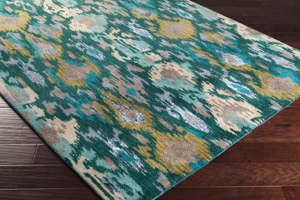 Hand-tufted patterned area rug from India with green, orange and teal on wood floor