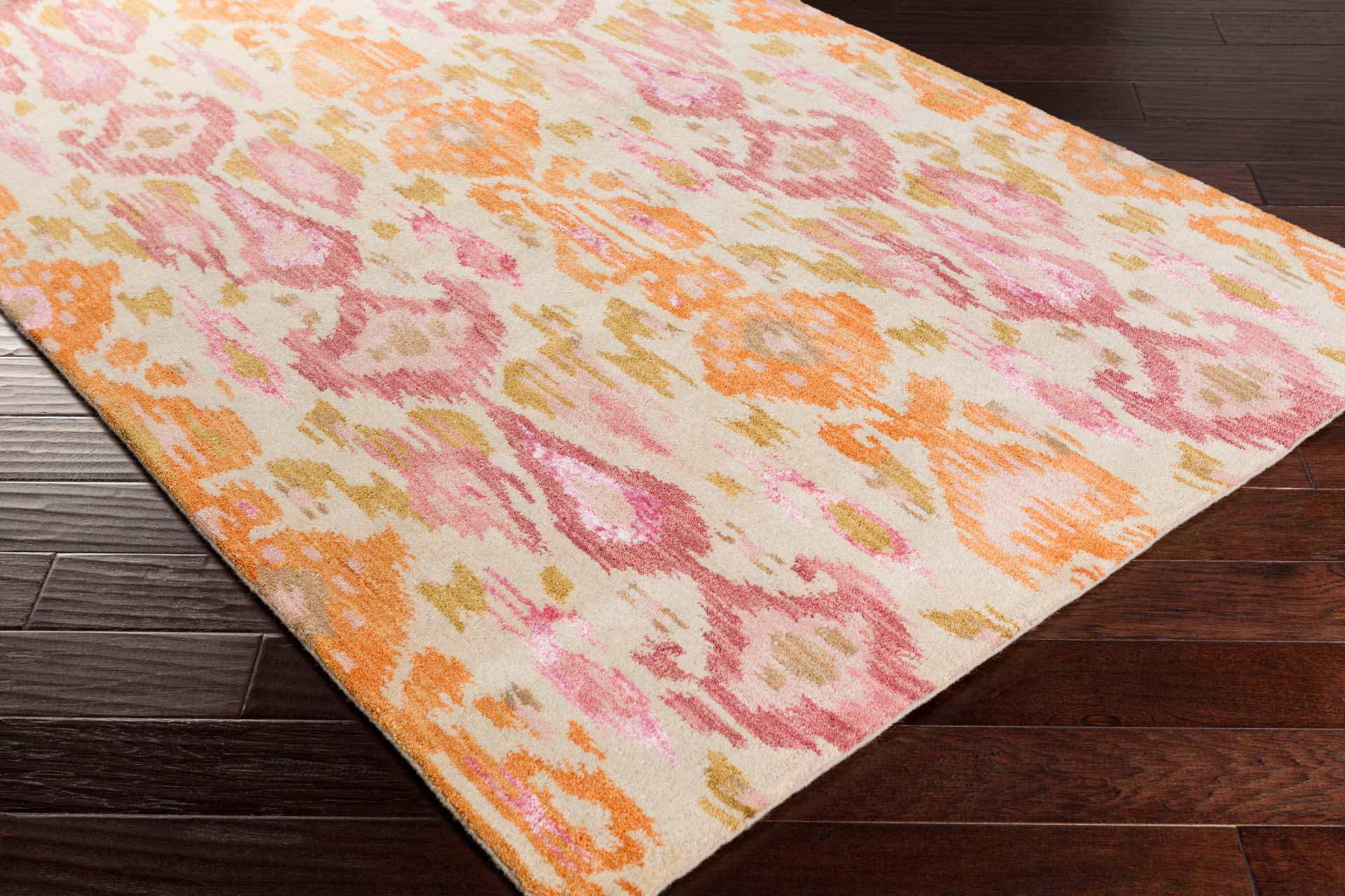 Contemporary hand-tufted area rug from India with bright yellow and pink pattern on wood floor