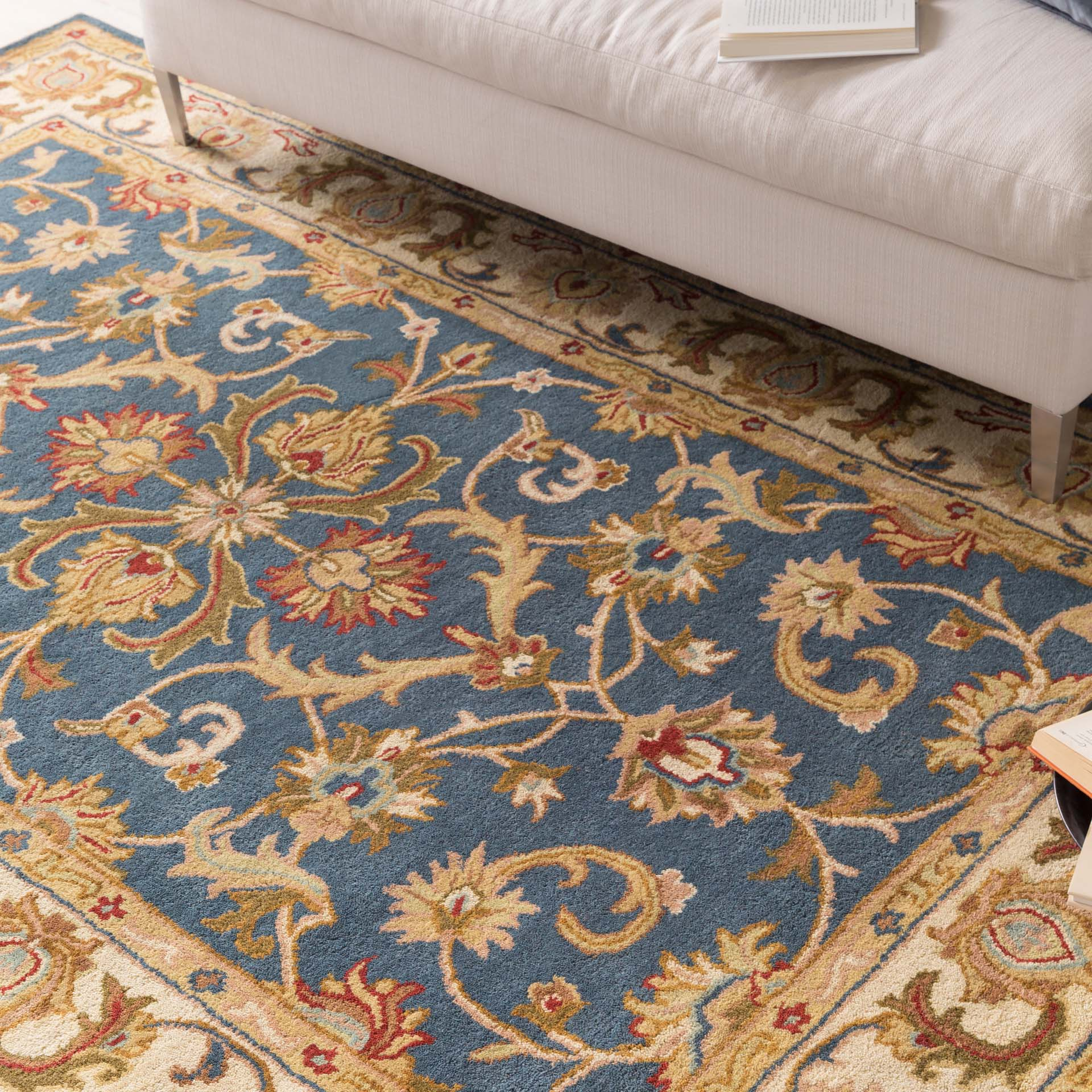 Classic hand-tufted area rug from India with cream, blue and red accents - Close up Shot