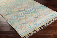 Hand woven area rug from India in pastel blue, pink and green with fringe on wood floor