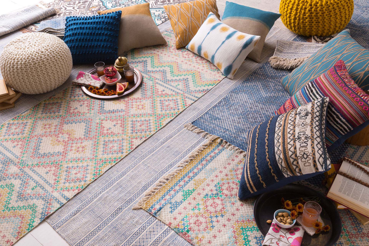 Hand woven area rug from India in pastel blue, pink and green with fringe with pillows on floor