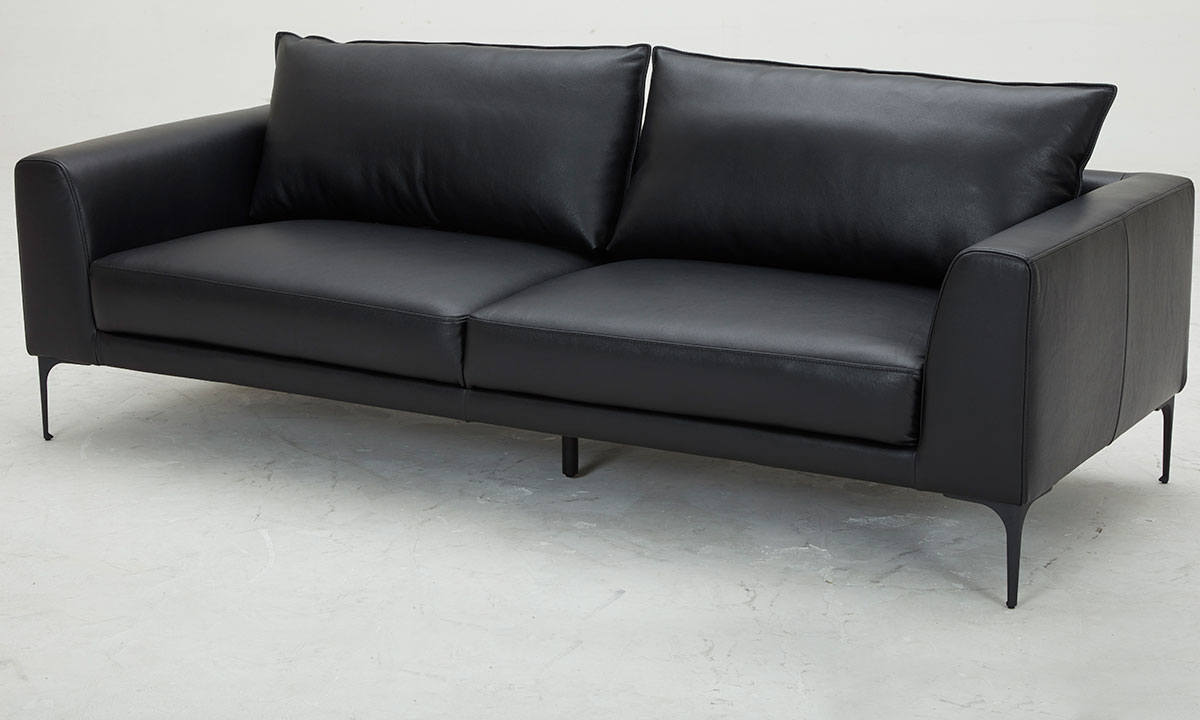 Modern and sleek pillowback sofa in black top-grain leather with vinyl match atop metal legs - Angled View