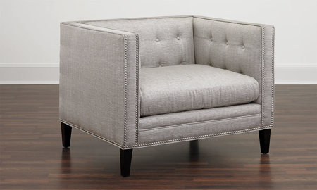Classic tuxedo chair with silver nailhead trim and dark wood feet in grey herringbone upholstery