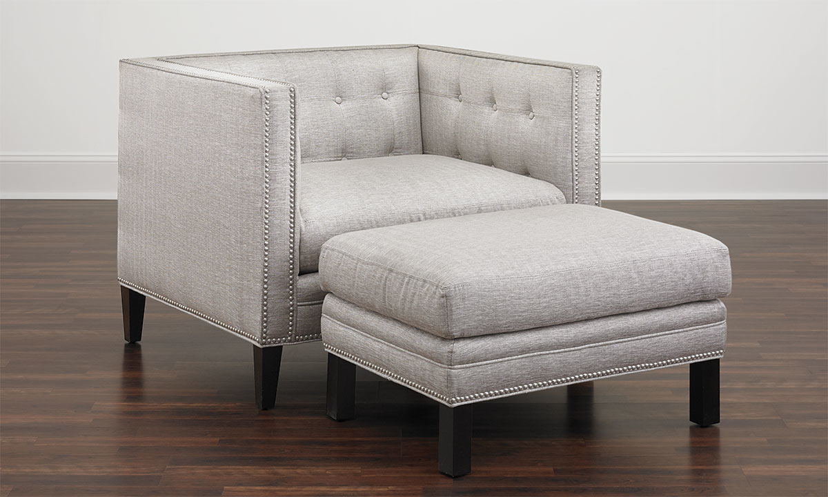 Classic tuxedo chair with silver nailhead trim and dark wood feet in grey herringbone upholstery with matching ottoman