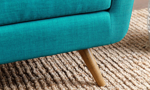 Close up of birch wood flare legs on retro sofa in teal linen-like upholstery