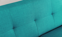 Close up of button tufting on retro sofa in teal linen-like upholstery