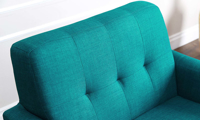 Close up of birch wood flare legs on retro arm chair in teal linen-like upholstery